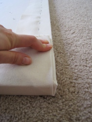 """Then fold the remaining canvas over your 45-degree fold, as shown. If the canvas peeks out over the edge of the stretcher, you'll have to readjust the first two folds. Even professional artists play this """"corner game,"""" so don't be discouraged if it's not initially perfect."""