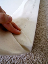 First lay the material along the edge that's parallel to you, pulling it tight. Next, pinch the canvas and overlap it on the pulled material, folding it over at a 45-degree angle.